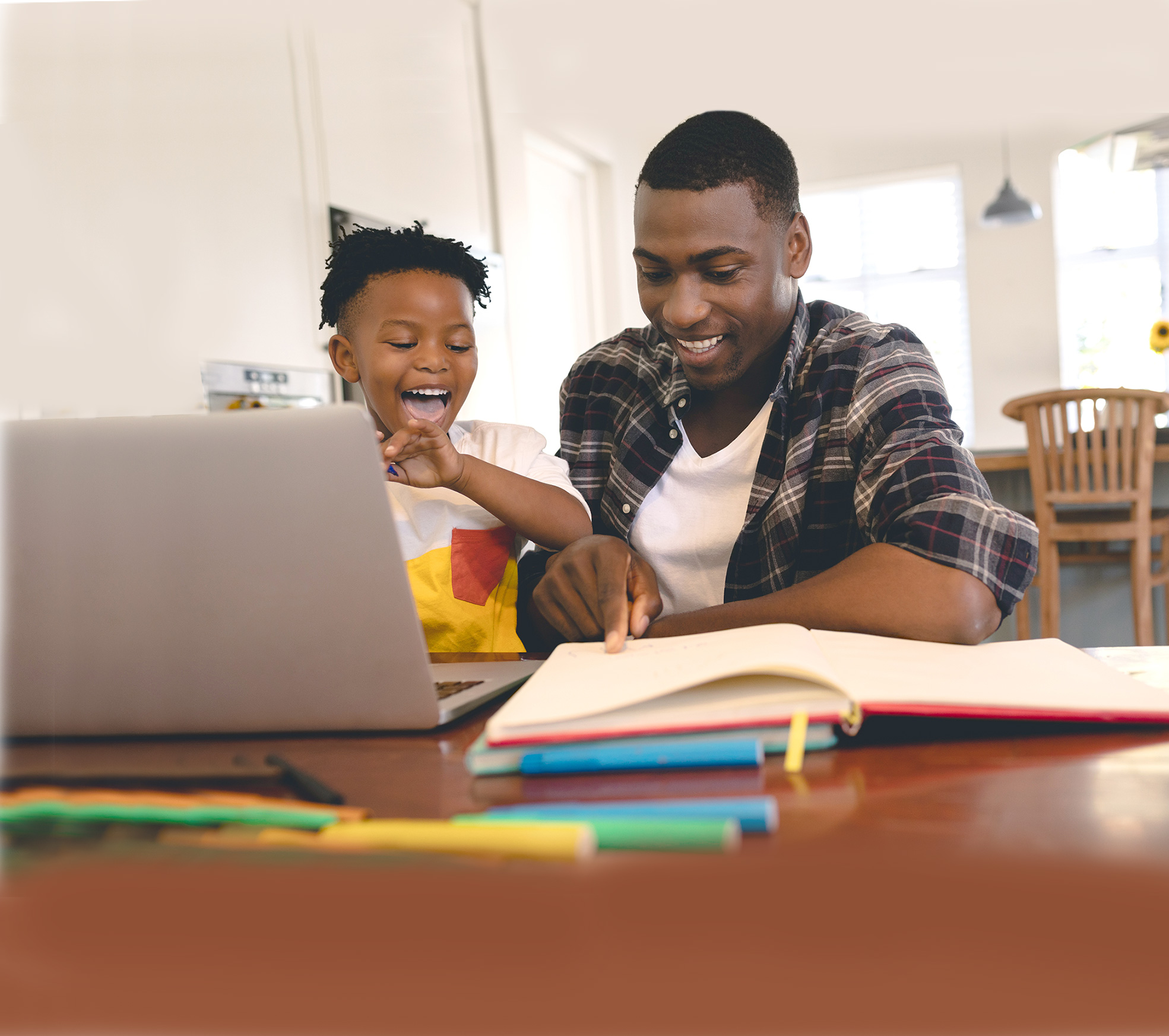 Man of colour and his son on computer at kitchen table smiling