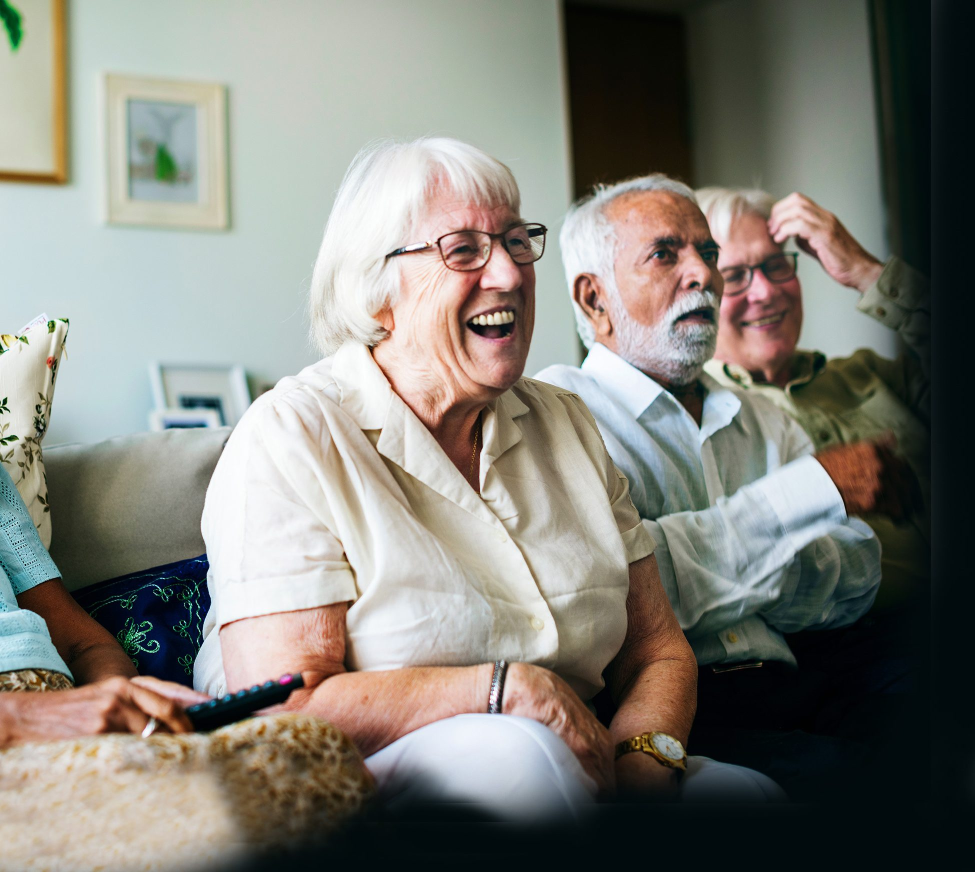 Pensioner in home laughing with others watching TV